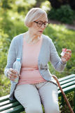 Concentrated aging woman holding bottle with pills outdoors. Time for everyday health routine. Thoughtful retired depressed lady feeling exhausted and holding stock photos