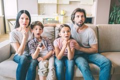 Concentrated, amazed and attractive family is sitting on sofa and watching. Mother and kods hold their hands under chin. Guy hugs his daughter royalty free stock image