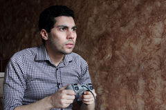 Concentrated arab egyptian businessman playing playstation. Image of arabian egyptian business man wearing shirt and feeling concentrated and worried while Royalty Free Stock Image