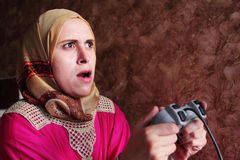 Concentrated arab egyptian muslim woman playing playstation. Image of arabian egyptian muslim woman wearing hijab and concentrated while playing playstation Royalty Free Stock Photos