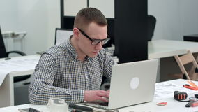 Concentrated architect designing new project on laptop stock video