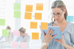 Concentrated artist with digital tablet and colorful sticky notes Royalty Free Stock Photography