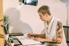 Concentrated artist with hands covered in tattoos carrying colored pencil royalty free stock photo