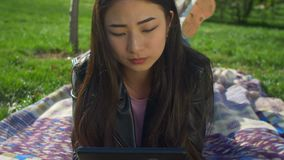 Concentrated asian girl working on tablet pc in park stock footage