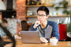 Concentrated asian man sitting in cafe, thinking and using laptop Royalty Free Stock Photo