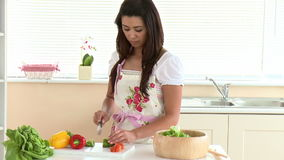 Concentrated asian woman preparing a salad stock footage