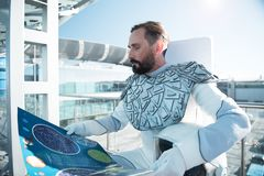 Concentrated astronaut reading space map Royalty Free Stock Image