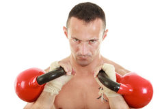 Concentrated athletic man holding red kettlebells weights lifted Stock Image
