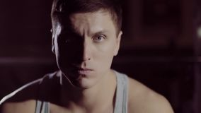 Concentrated athletic young man looking into the camera under artificial light stock footage