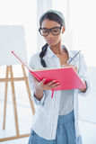 Concentrated attractive artist drawing on her notebook Royalty Free Stock Images