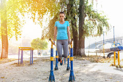 Concentrated attractive sportswoman doing push ups outdoors. Front view of concentrated attractive sportswoman doing push ups outdoors Royalty Free Stock Images