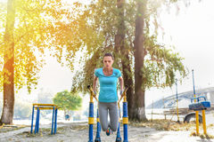 Concentrated attractive sportswoman doing push ups outdoors. Front view of concentrated attractive sportswoman doing push ups outdoors Stock Photography