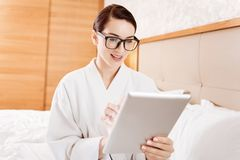 Concentrated  attractive woman holding tablet. Preparation for presentation.  Beautiful  young budding woman working on presentation while looking at the tablet Stock Image