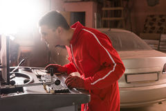 Concentrated auto mechanic checking the readout on a computer. Hooked to a car elevated on a hoist as he performs a service and tune up in a garage workshop Stock Image