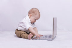 Concentrated baby boy playing in laptop. Concept of IT generation. Gamer. stock photos