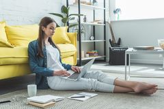 concentrated barefoot girl using laptop while sitting on carpet and studying royalty free stock photography