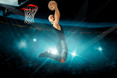 Concentrated basketball player in black jersey makes reverse sla Stock Photos