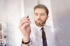 Concentrated bearded businessman in shirt touching screen interface. And drawing a chart in office Stock Photo