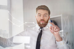 Concentrated bearded businessman in shirt touching screen interface. And drawing a chart in office Royalty Free Stock Images