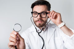 Concentrated bearded man holding stethoscope. Royalty Free Stock Images