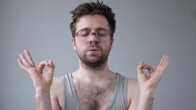 Concentrated bearded man in huge glasses meditates, tries to relax keeps fingers together