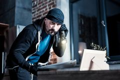 Concentrated bearded thief stealing a laptop stock photography
