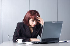 The concentrated beautiful business woman. Behind a desktop and the laptop Royalty Free Stock Image