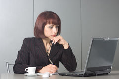 The concentrated beautiful business woman. Behind a desktop and the laptop Royalty Free Stock Photography