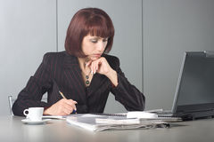 The concentrated beautiful business woman. Behind a desktop and the laptop Stock Image