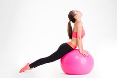 Concentrated beautiful fitness girl doing sport with fitball Royalty Free Stock Images