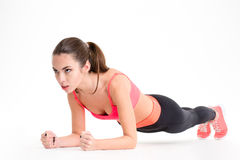 Concentrated beautiful fitness girl in sportwear exercising doing plank royalty free stock photo