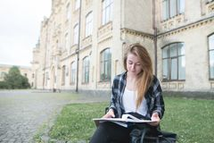 Concentrated beautiful girl student sitting on a bench on college campus and reading. Beautiful girl in casual clothes outdoors studying at university. Student stock images