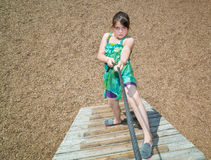 Concentrated beautiful little girl climbing on wooden stairs at kids play ground Royalty Free Stock Image