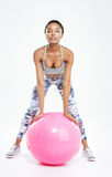 Concentrated beautiful young african american sportswoman working out with fitball Royalty Free Stock Images