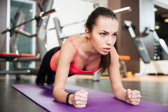 Concentrated beautiful young sportswoman doing plank exercise. On mat in gym Royalty Free Stock Photography