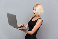 Concentrated beautiful young woman hoding and using laptop Stock Photos