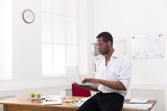 Concentrated black businessman in casual office, work with laptop Stock Photo