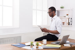 Concentrated black businessman in modern office, work with tablet Royalty Free Stock Photo