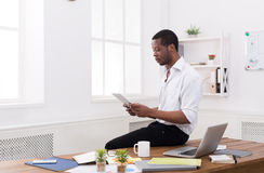 Concentrated black businessman in modern office, work with tablet Royalty Free Stock Photography