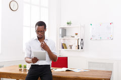 Concentrated black businessman in modern office, work with tablet. Concentrated african-american businessman in office, searching for new ideas on tablet Royalty Free Stock Images