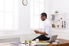 Concentrated black businessman in modern office, work with tablet. Concentrated african-american businessman in office, searching for new ideas on tablet Royalty Free Stock Photo
