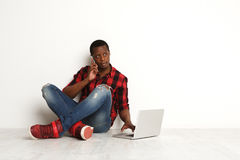 Concentrated black man using mobile and laptop sitting on the studio floor Royalty Free Stock Images