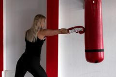 Concentrated blond woman in red boxing gloves in black sportswear doing boxing training with a punching bag. Girl in the boxing gym beats a punching bag royalty free stock photo
