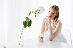 Concentrated blonde lad holding glass of water. Image of concentrated blonde lady sitting indoors near flowers dressed in white dress. Looking aside holding Royalty Free Stock Photography