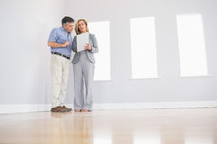 Concentrated blonde realtor showing a room and some documents to Stock Images