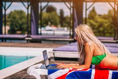 Concentrated Blondie Young Woman Is Laying On The Deck Chair And Typing On Her Laptop Near The Pool. Green Bikini.Blue Water royalty free stock photos