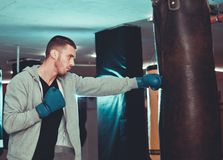 Concentrated boxer direct hit with punching bag. At gym stock photos