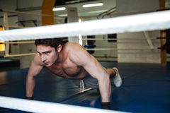 Concentrated Boxer doing push ups in gym. Concentrated Boxer with naked torso doing push ups in boxing ring in gym royalty free stock image