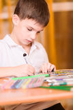 Concentrated boy colouring book portrait. Concentrated boy colouring book close up Royalty Free Stock Photos