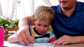Concentrated boy drawing in a cafe with his father stock video